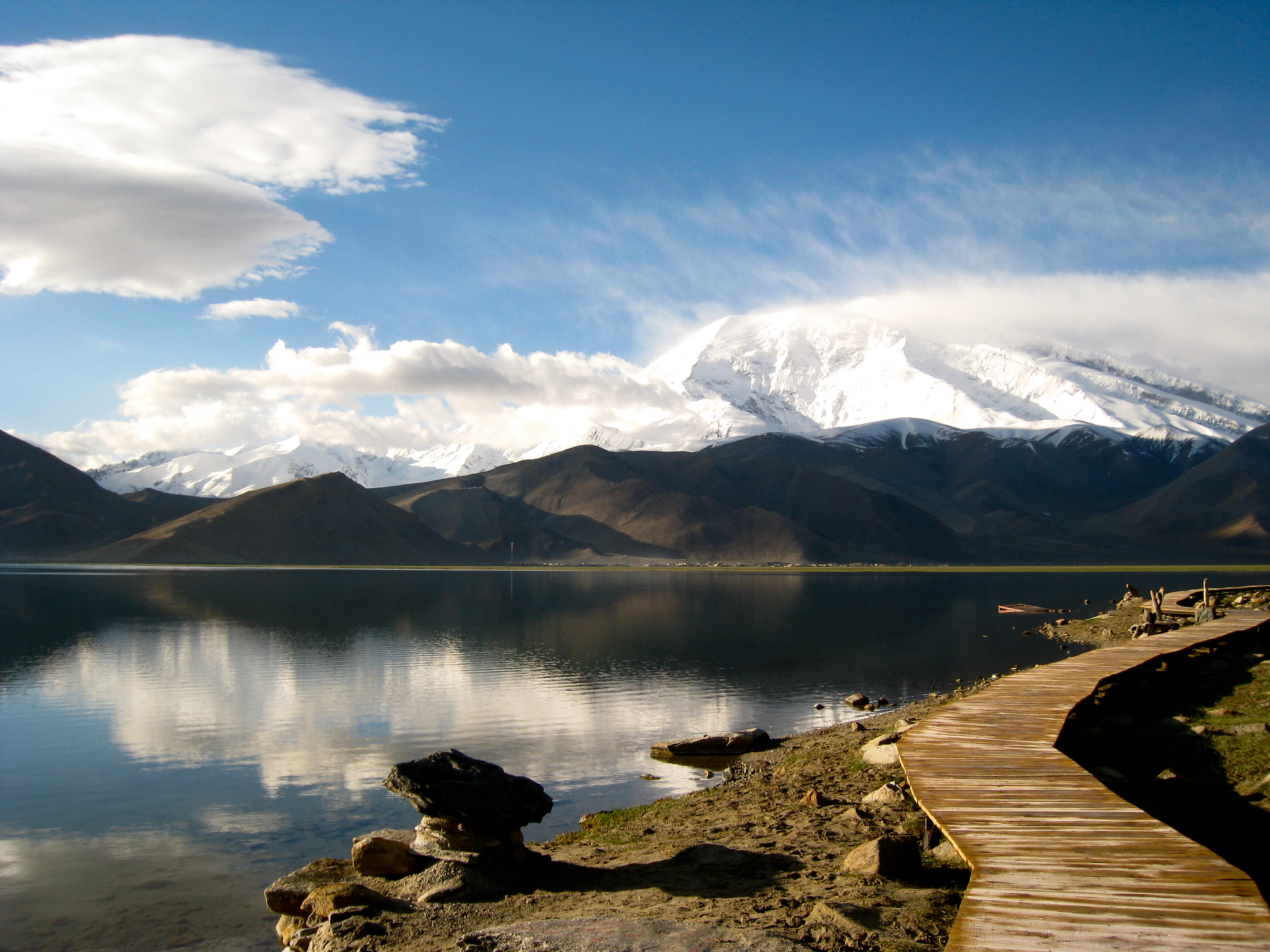 Picture of water, mountains and a wooden walking path